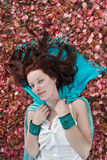 Mulher nova que coloca na terra coberta com as pétalas Fotos de Stock Royalty Free