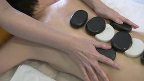 Mulher nova que começ a massagem de pedra quente no salão de beleza dos termas Conceito do tratamento da beleza vídeos de arquivo