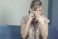 Mulher nova que começ a notícia ruim pelo telefone imagem de stock royalty free