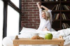 Mulher nova que come o pequeno almoço na cama Imagens de Stock Royalty Free