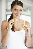 Mulher nova que come o rolo de pão de Brown Fotos de Stock