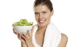 Mulher nova que come a salada após a aptidão fotografia de stock