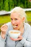 Mulher nova que come uma bacia de cereal Fotografia de Stock Royalty Free