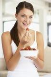 Mulher nova que come uma bacia de morangos frescas Imagens de Stock