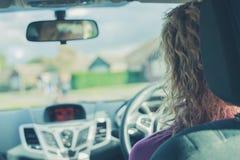 Mulher nova que conduz o carro Fotografia de Stock