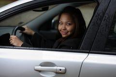Mulher nova que conduz seu carro novo. fotografia de stock