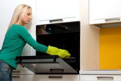 Mulher nova que cozinha com forno Fotos de Stock