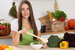 Mulher nova que cozinha na cozinha Householding, alimento saboroso e vegetariano em conceitos do estilo de vida imagens de stock royalty free