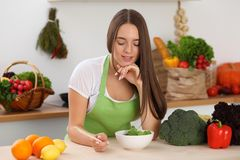 Mulher nova que cozinha na cozinha Householding, alimento saboroso e vegetariano em conceitos do estilo de vida imagem de stock