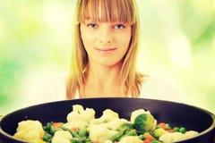 Mulher nova que cozinha o alimento Fotografia de Stock