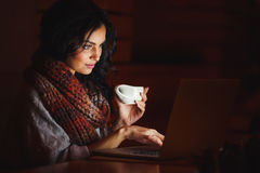 Mulher nova que datilografa em um portátil Foto de Stock