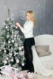 Mulher nova que decora a árvore de Natal Fotos de Stock