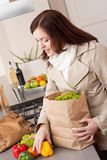 Mulher nova que desembala o saco de compra na cozinha Imagem de Stock
