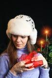Mulher nova que desempacota o presente do Natal imagem de stock
