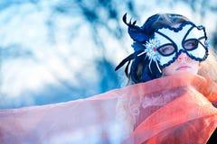 Mulher nova que desgasta a máscara vermelha do carnaval fotografia de stock