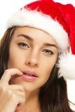 A mulher nova que desgasta o chapéu de Santa põr sua ponta do dedo t Imagens de Stock