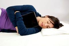 Mulher nova que dorme com computador da tabuleta Fotografia de Stock