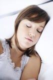 Mulher nova que dorme na cama Foto de Stock