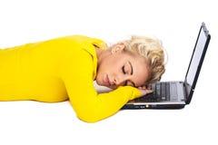 Mulher nova que dorme no portátil imagem de stock