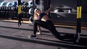 Mulher nova que elabora na ginástica Mulher delgada que faz esticando o exercício na luz solar da manhã no gym moderno filme