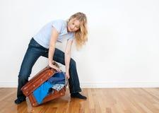 Mulher nova que embala uma mala de viagem Imagens de Stock