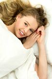 Mulher nova que encontra-se na cama Fotografia de Stock Royalty Free
