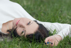Mulher nova que encontra-se na grama Imagem de Stock
