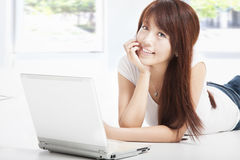 Mulher nova que encontra-se no assoalho que faz trabalhos de casa Imagens de Stock Royalty Free