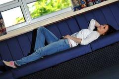 Mulher nova que encontra-se no sofá Fotografia de Stock