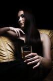 Mulher nova que encontra-se no sofá com um vidro do uísque imagem de stock