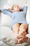 Mulher nova que encontra-se no sofá, foco em seus pés fotografia de stock