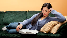 Mulher nova que encontra-se para baixo no sofá e no livro de leitura Fotografia de Stock