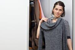 Mulher nova que escolhe a roupa Fotografia de Stock Royalty Free