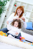 Mulher nova que escova o cabelo da sua filha foto de stock royalty free