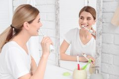Mulher nova que escova seus dentes imagem de stock