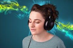 Mulher nova que escuta a música com auscultadores Foto de Stock