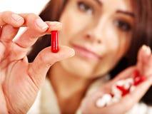 A mulher nova que está com a gripe toma comprimidos. Imagem de Stock