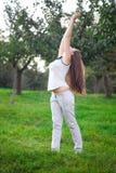 Mulher nova que está na grama verde Fotos de Stock Royalty Free