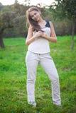 Mulher nova que está na grama verde Fotos de Stock