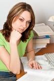 Mulher nova que estuda o assento em uma tabela Fotos de Stock