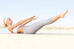 Mulher nova que exercita na praia Foto de Stock Royalty Free