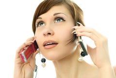 Mulher nova que fala em dois cell-phones Fotografia de Stock Royalty Free
