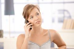 Mulher nova que fala no móbil em casa foto de stock royalty free
