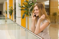 Mulher nova que fala no telemóvel na alameda Imagens de Stock
