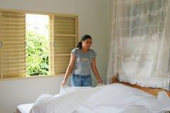 Mulher nova que faz a cama Fotografia de Stock