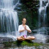 Mulher nova que faz a ioga perto das cachoeiras Fotografia de Stock