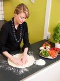 Mulher nova que faz a massa de pão da pizza Imagem de Stock