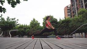 A mulher nova que faz o esticão exercita ao ar livre vídeos de arquivo