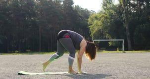 Mulher nova que faz o exercício da ioga ao ar livre vídeos de arquivo