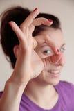 Mulher nova que faz o sinal APROVADO Imagem de Stock